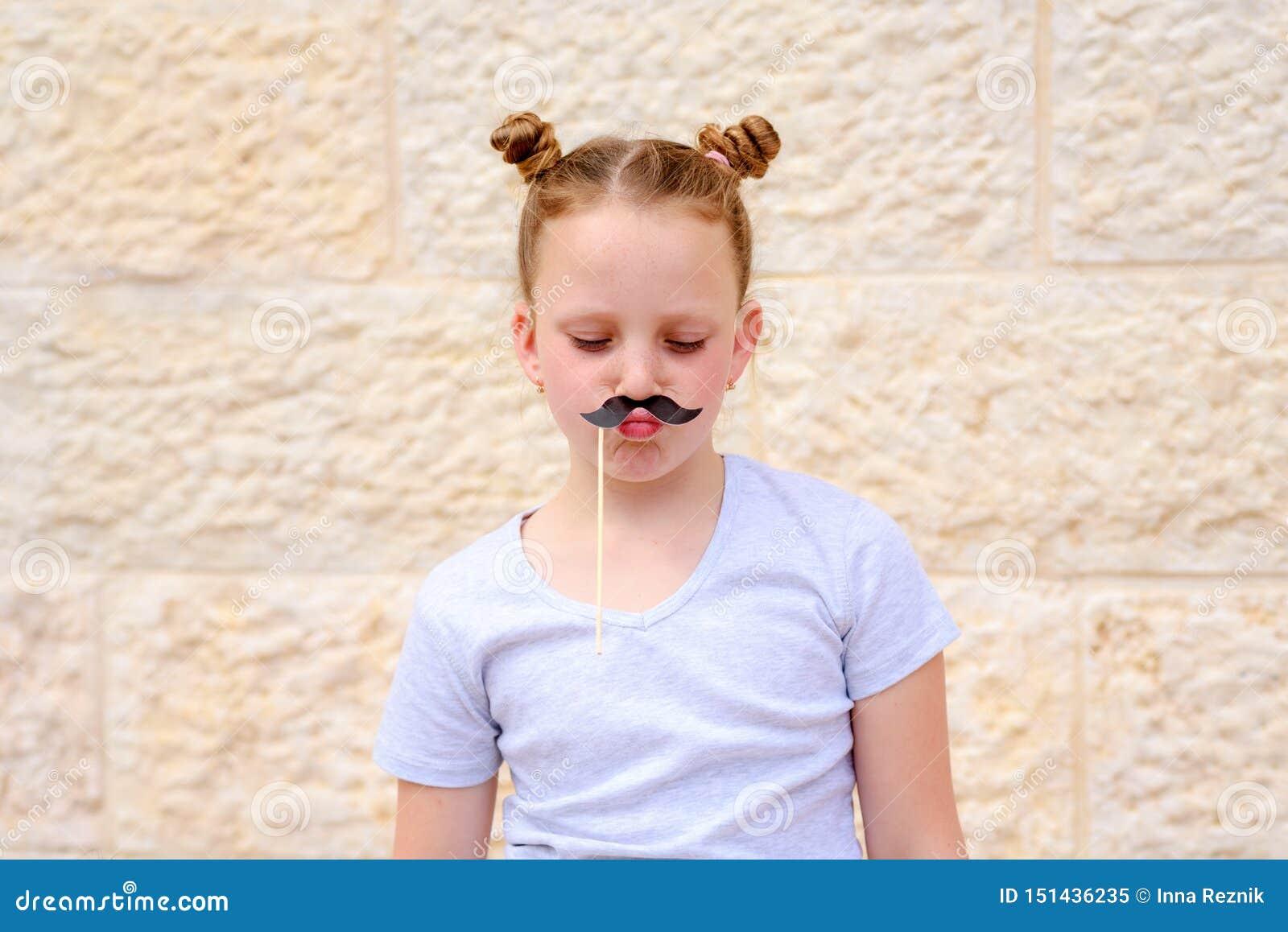 Rolig liten flicka med pappers- mustaschkarnevalmaskeringar som har gyckel på vit väggbakgrund