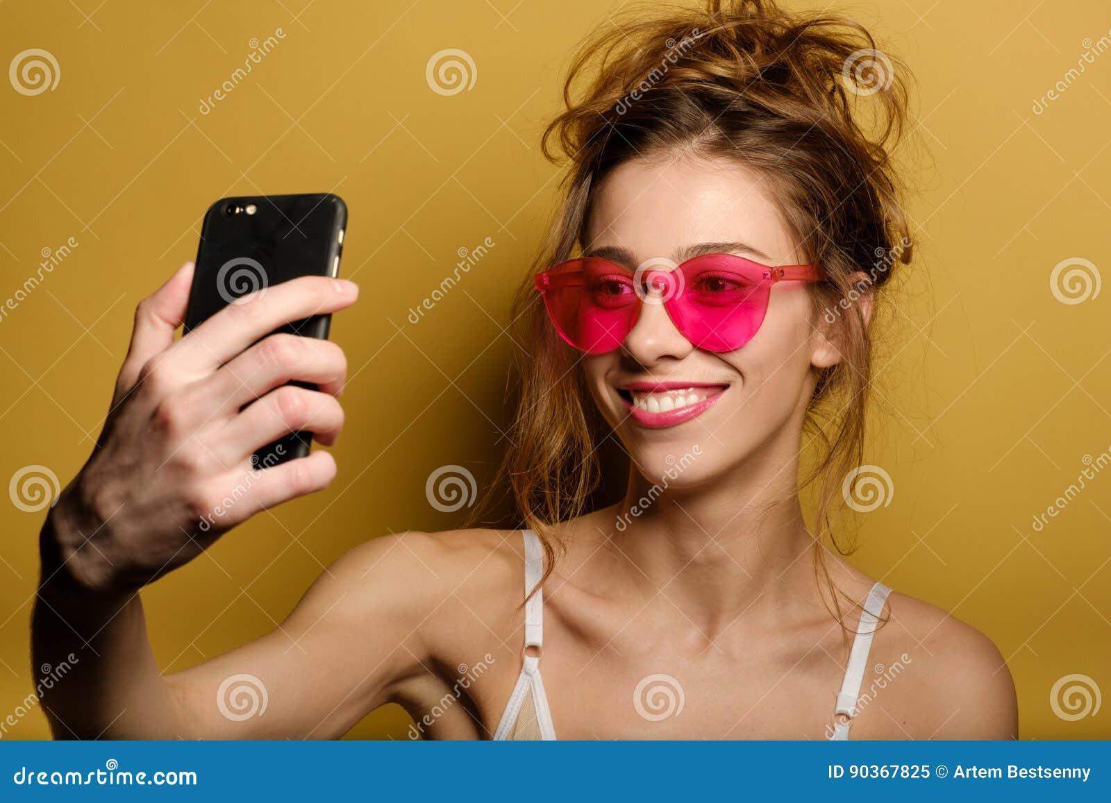 Rolig stående av en le ung flicka i rosa exponeringsglas, som gör selfie på telefonen på gul bakgrund