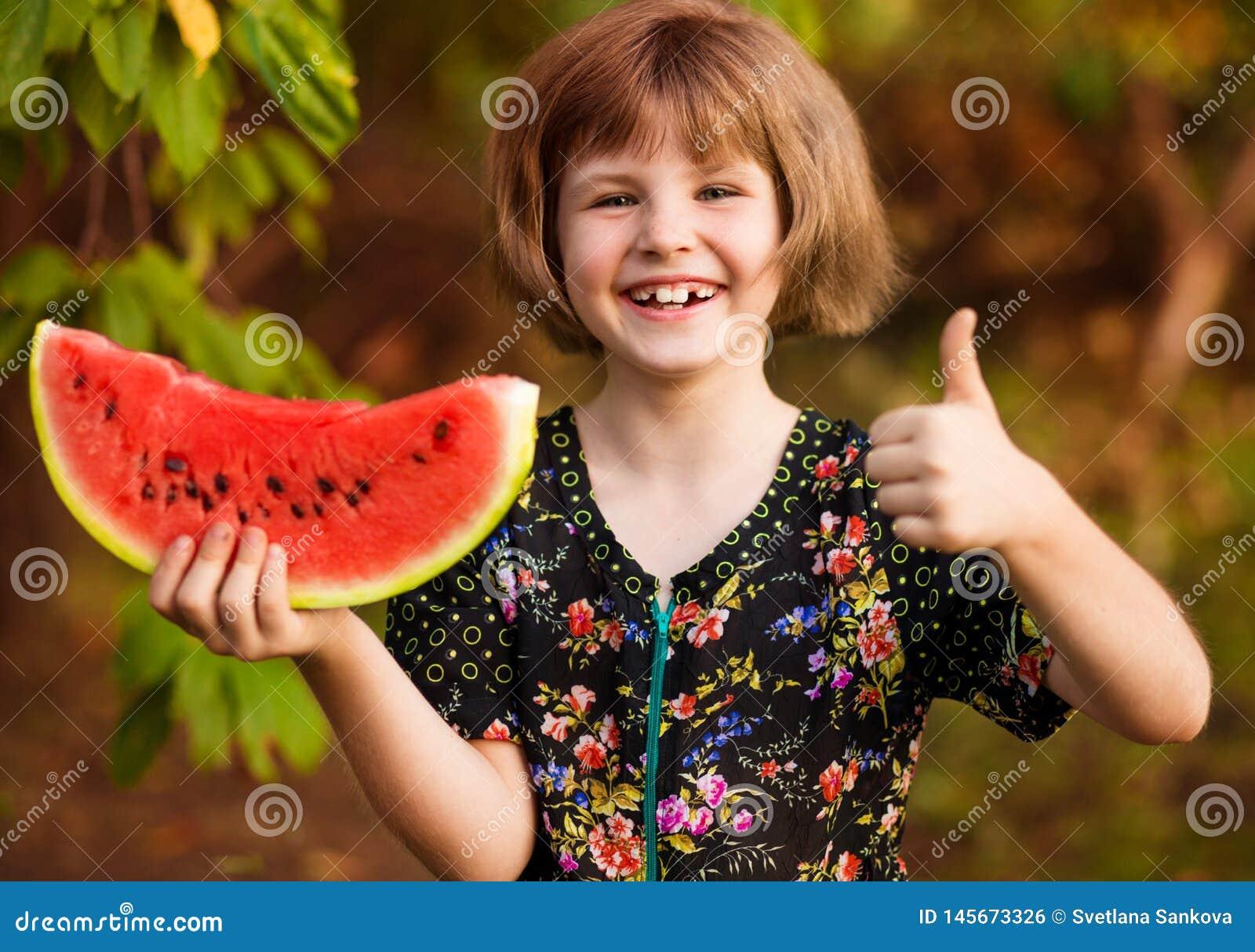 Rolig st?ende av den incredibly h?rliga lilla flickan som ?ter vattenmelon, sunt fruktmellanm?l