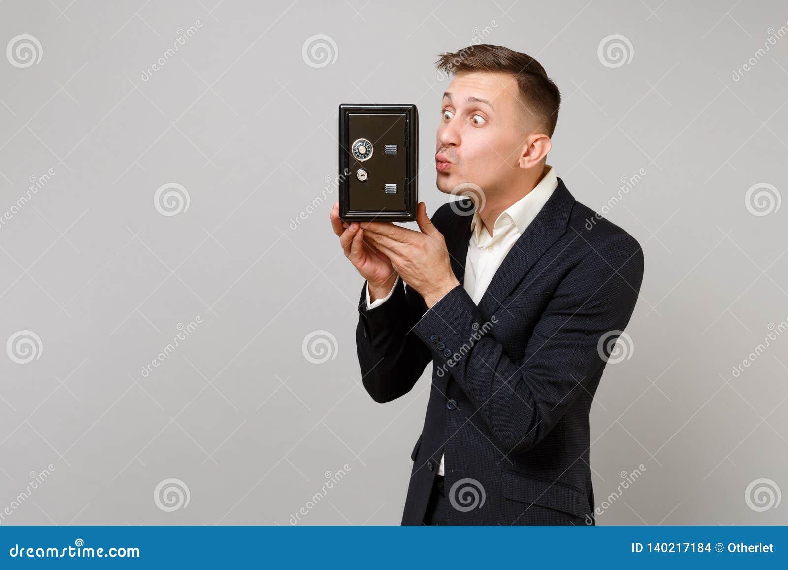 Rolig ung affärsman i dräkt som blåser överföra luftkyssen för att belägga med metall banken som är säker för pengarackumulation