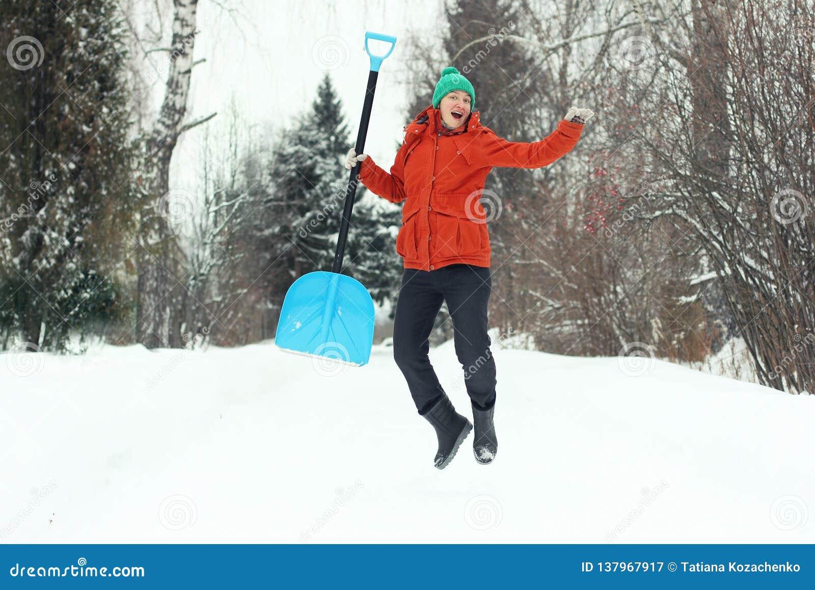 Rolig ung kvinna som hoppar med snöskyffeln på den lantliga vägen Säsongsbetonat begrepp för vinter