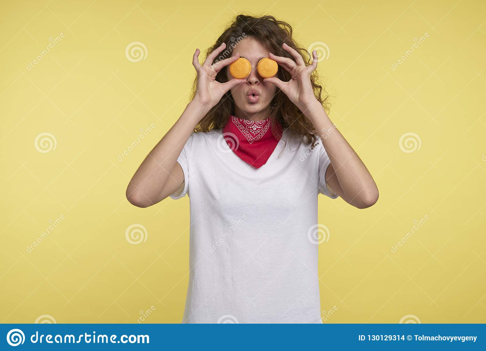 Rolig ung kvinna som rymmer makron nära ögon, mot gul bakgrund