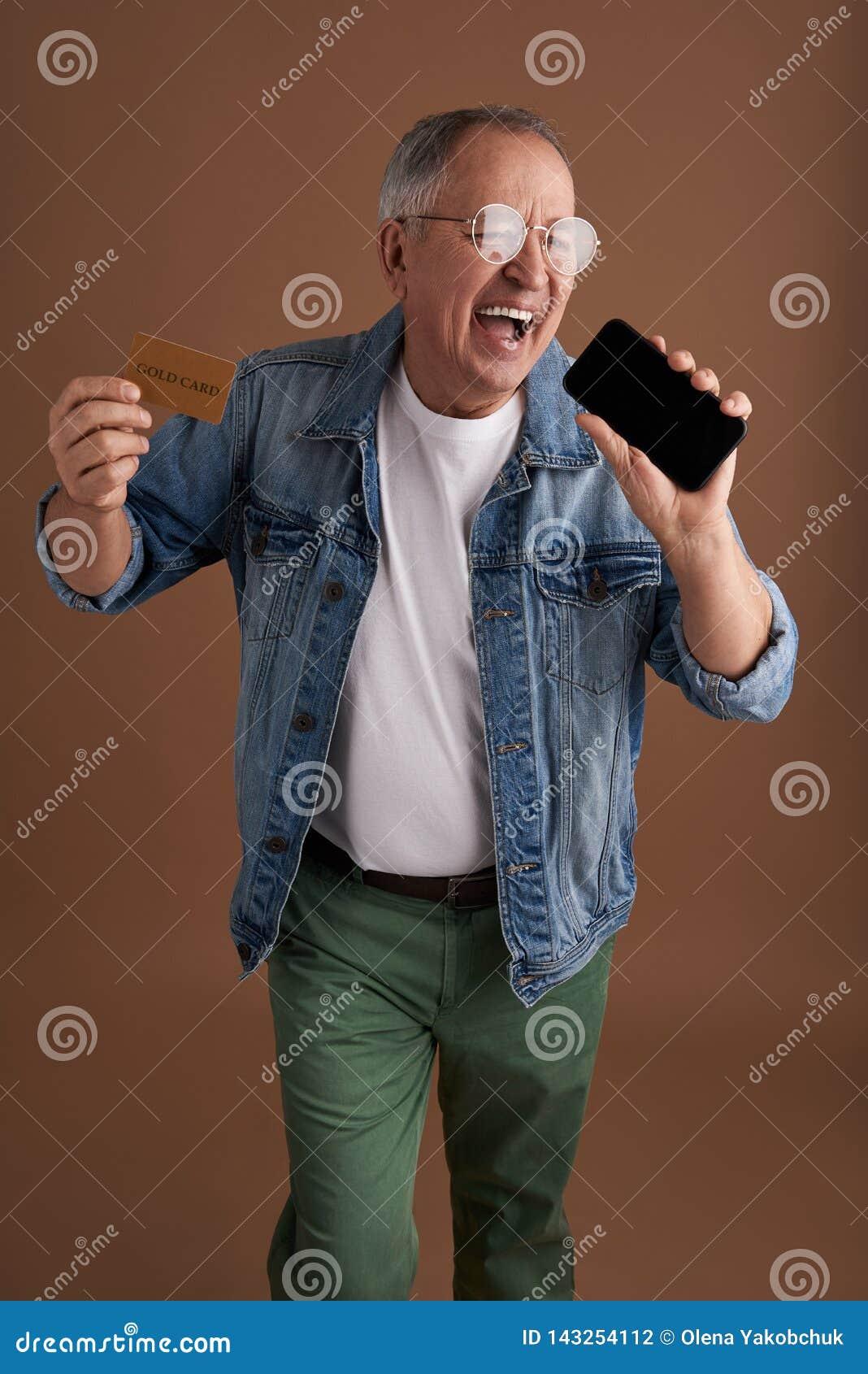 Rolig vuxen man som skryter hans nya smartphone och guld- kort
