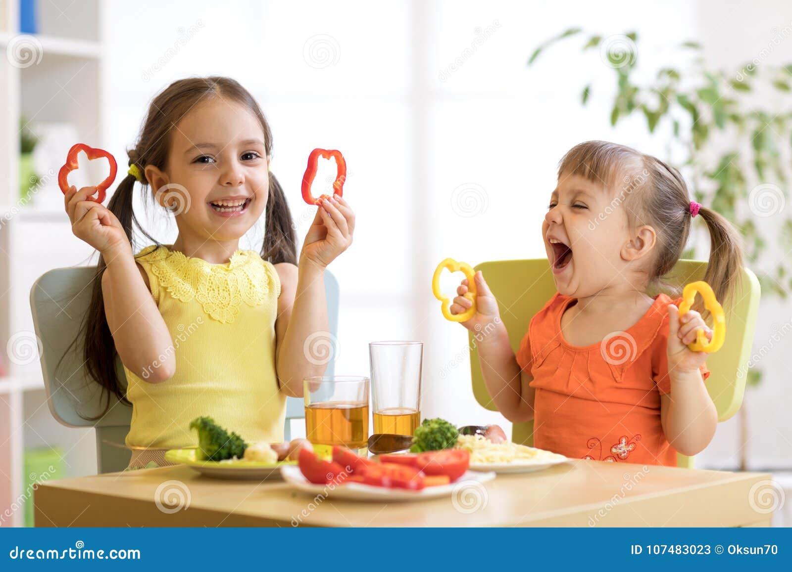 Roliga barnflickor som äter sund mat Ungar äter lunch hemma eller dagiset