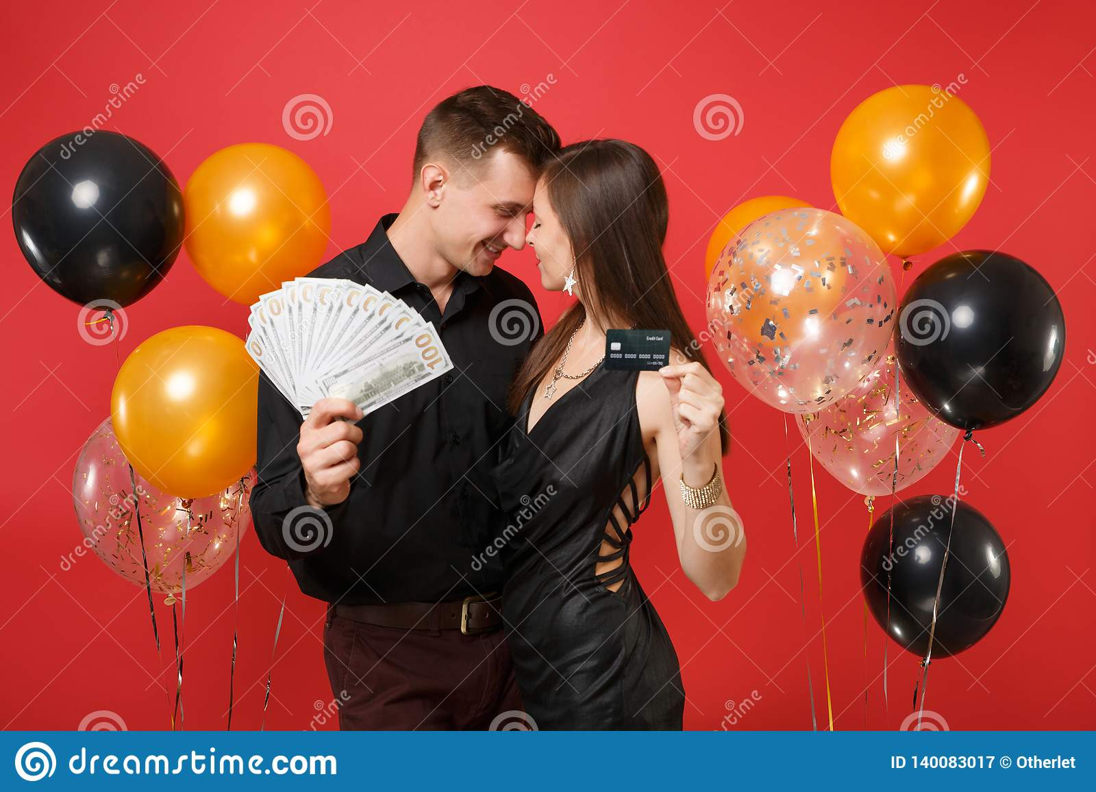 Roliga par som firar pengar för kassa för lott för håll för födelsedagferieparti, kreditkort som isoleras på ljus röd bakgrundslu