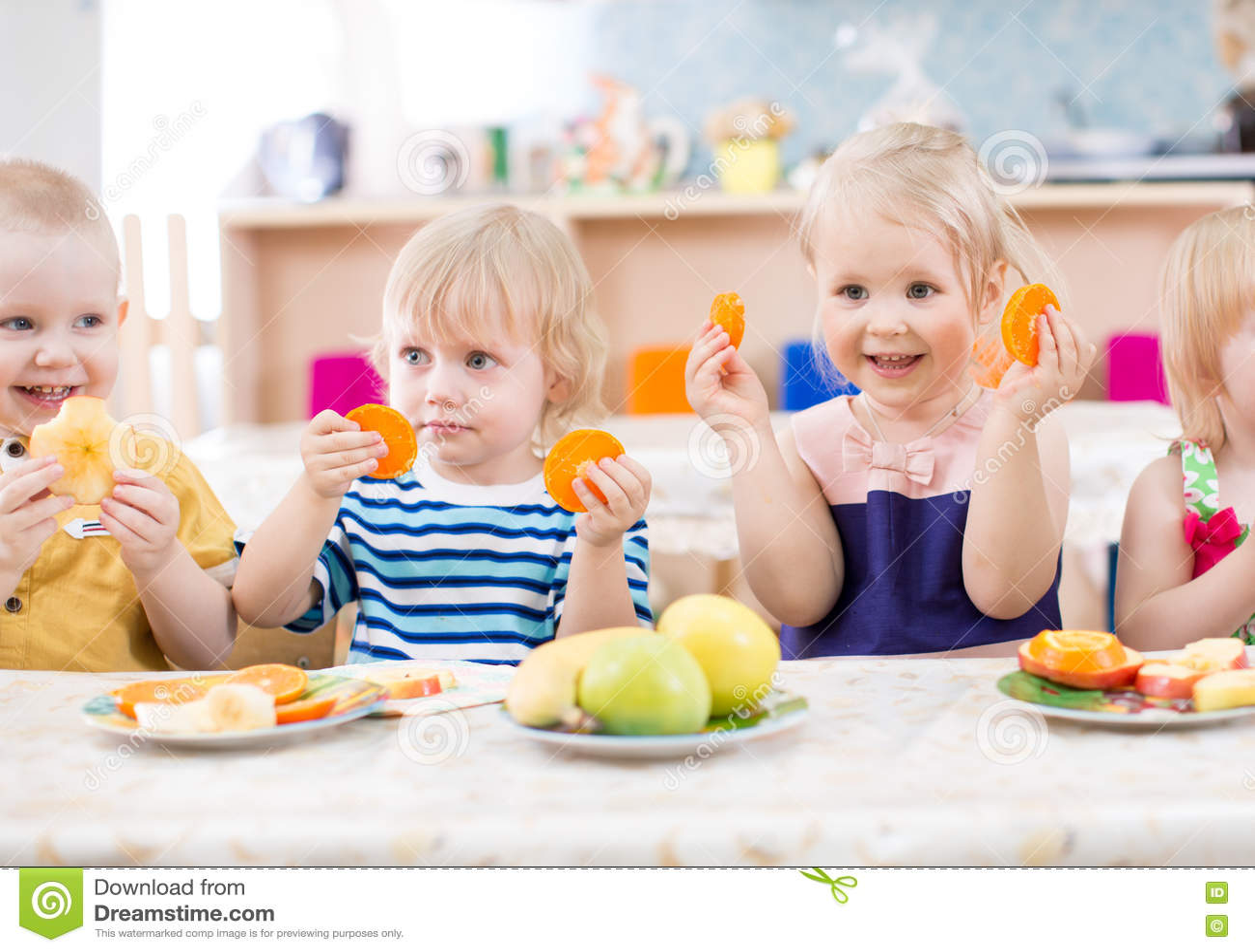 Roliga ungar som äter frukter i dinning rum för dagis