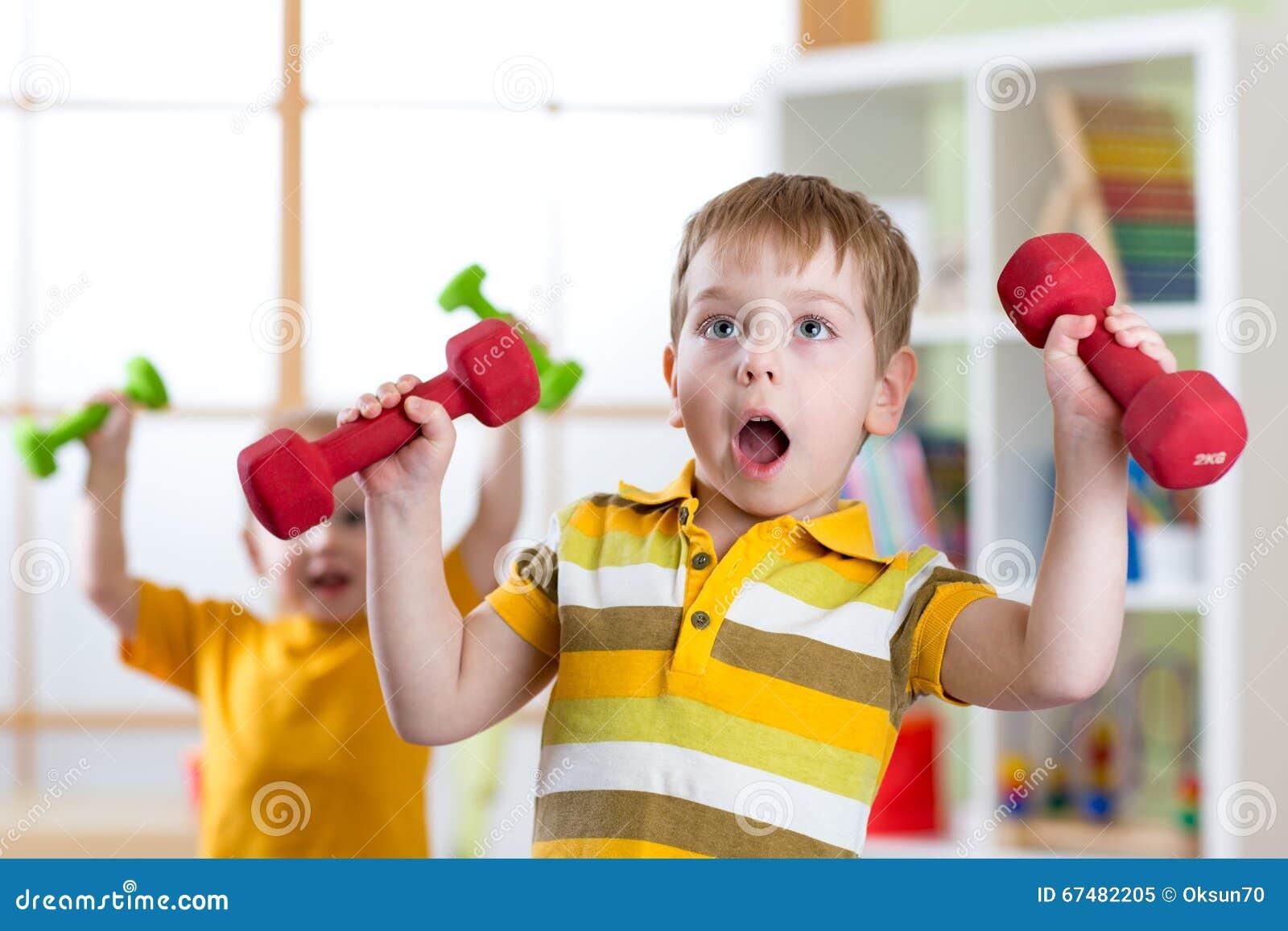 Roliga ungepojkar som övar med hemmastadda hantlar Sunt liv sportive barn