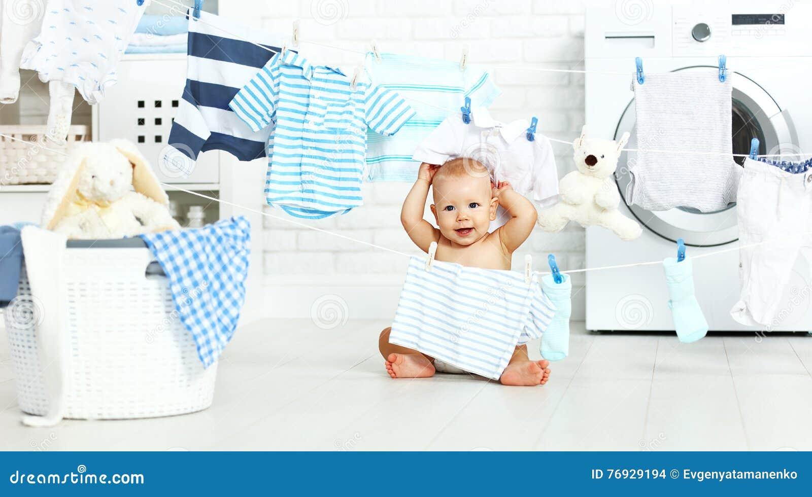 Roligt lyckligt behandla som ett barn pojken för att tvätta kläder och skratt i tvätteri