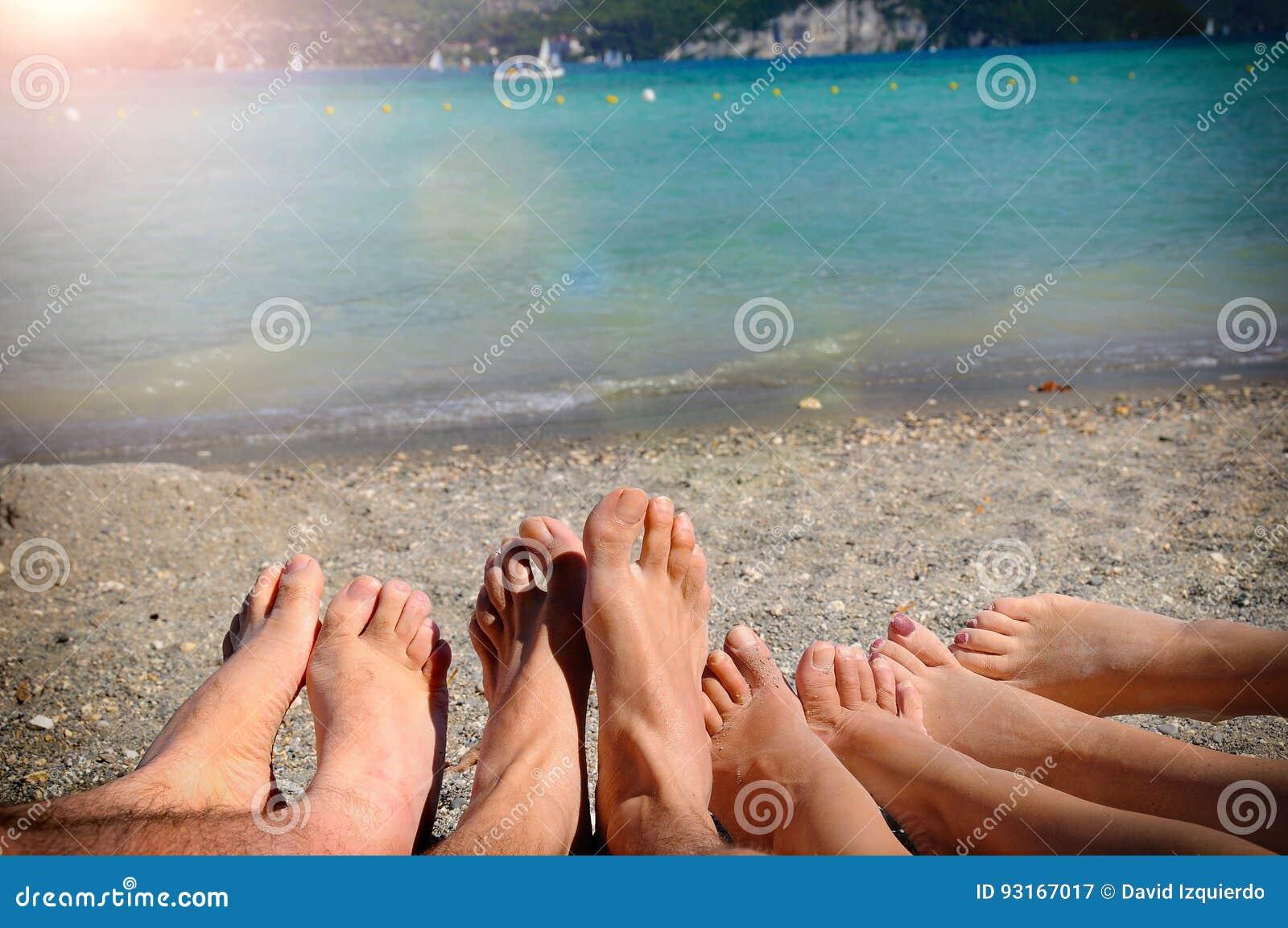Roligt turismbegrepp med fot av turister som ligger på sand
