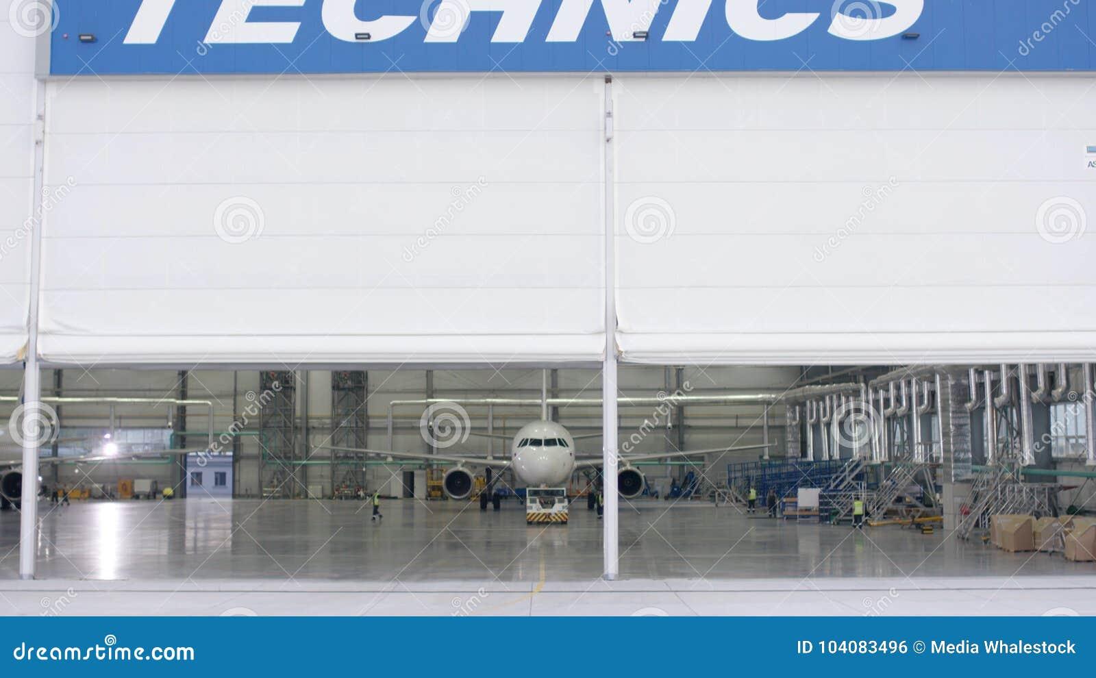 Rolkowy żaluzi drzwi i beton podłoga lotniskowy tło hangaru i samolotu Lotniskowy hangar od outside z