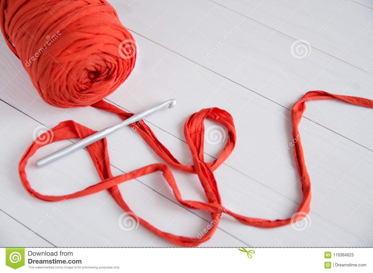 Roll The Cotton Yarn And Crochet Hook On White Wooden