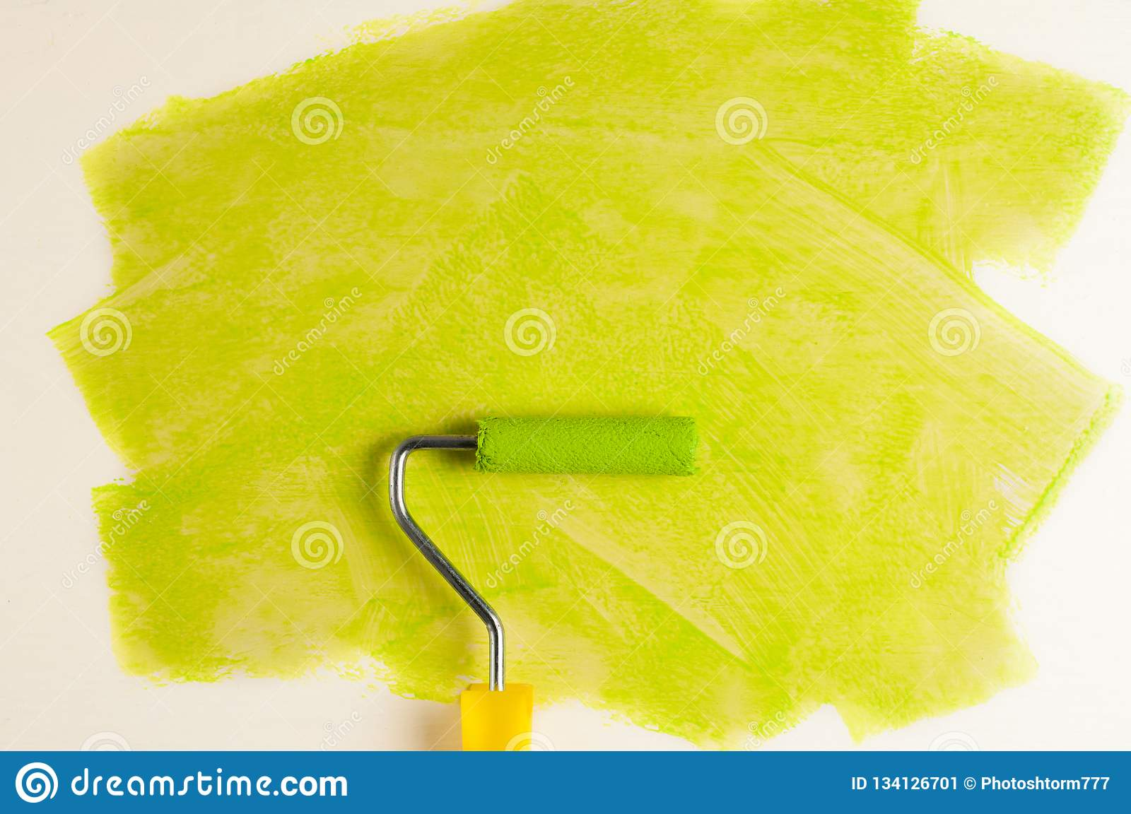 Roll for paint and green track on wall. Repair concept