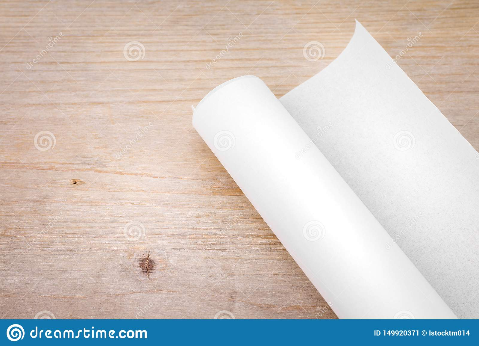 Roll of paper on wood table background. Engineer blueprint for draft work. Blank document for your design