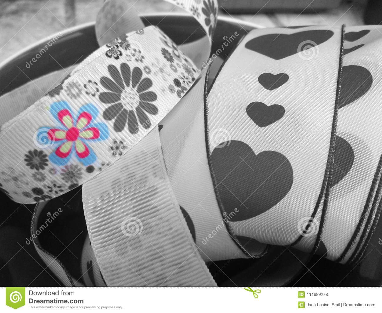 A Roll Of Ribbon Decorated With Hearts And Flowers Done In Grey Splash Colour