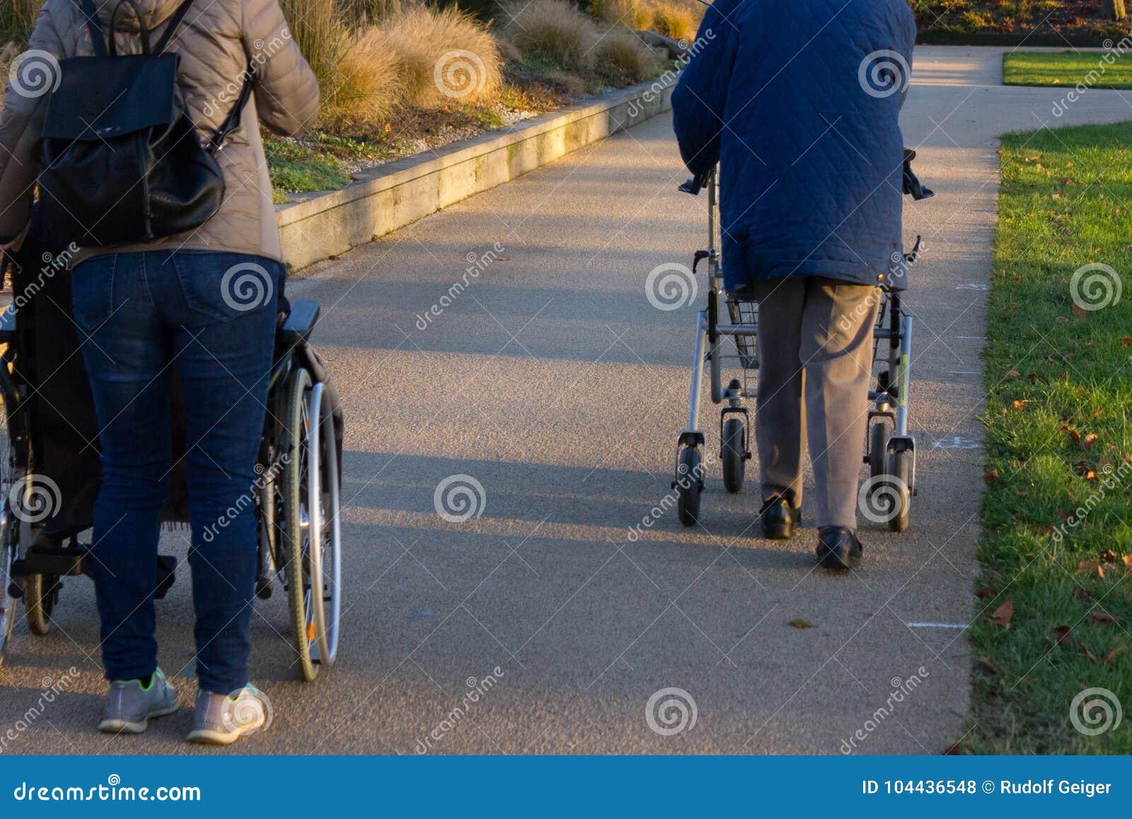 Rollator y silla de ruedas con el mayor en el parque histórico
