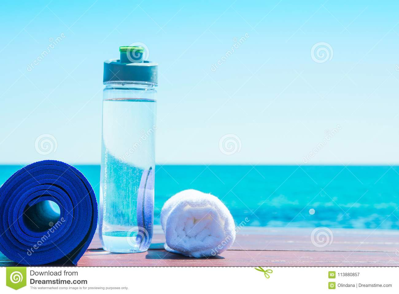 Rolled Yoga Mat Bottle with Water White Towel on Beach with Turquoise Sea Blue Sky in Background. Sunlight. Relaxation Meditation