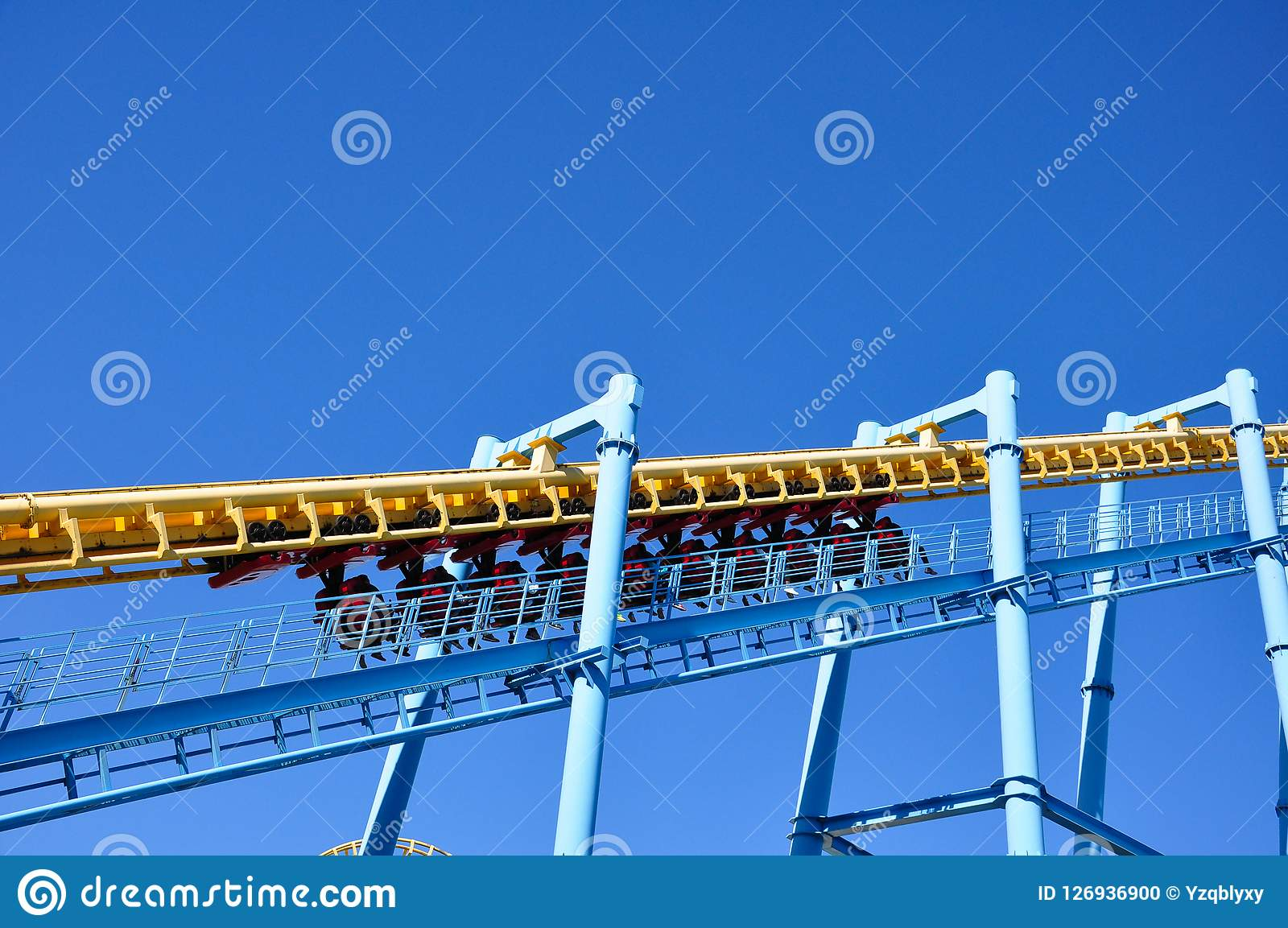 The roller coaster is starting on a sunny day