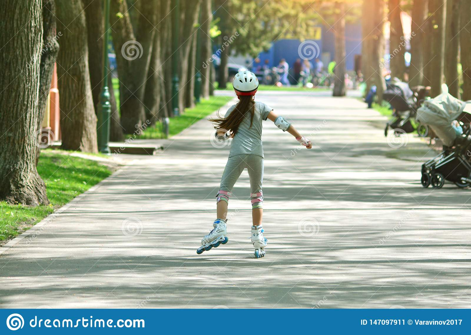Roller girl children on a park alley