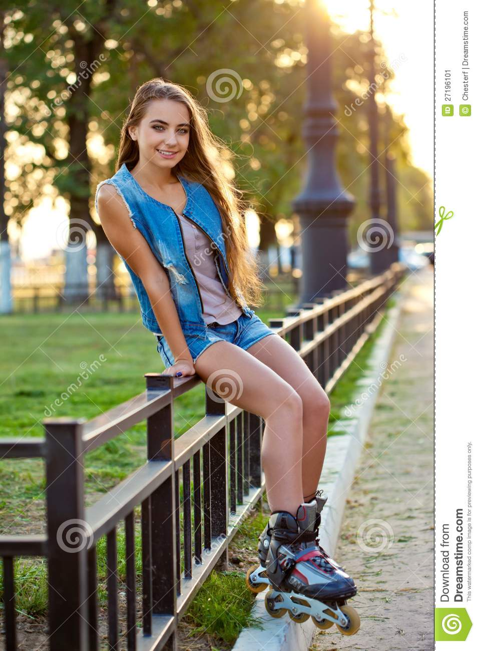 roller girl wearing jeans sitting on iron fence stock
