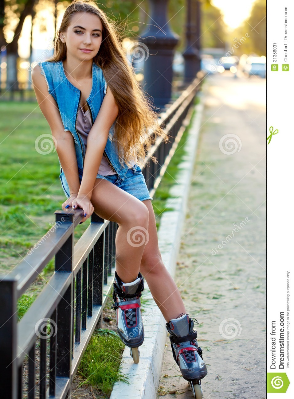 roller girl wearing jeans sitting on iron fence royalty