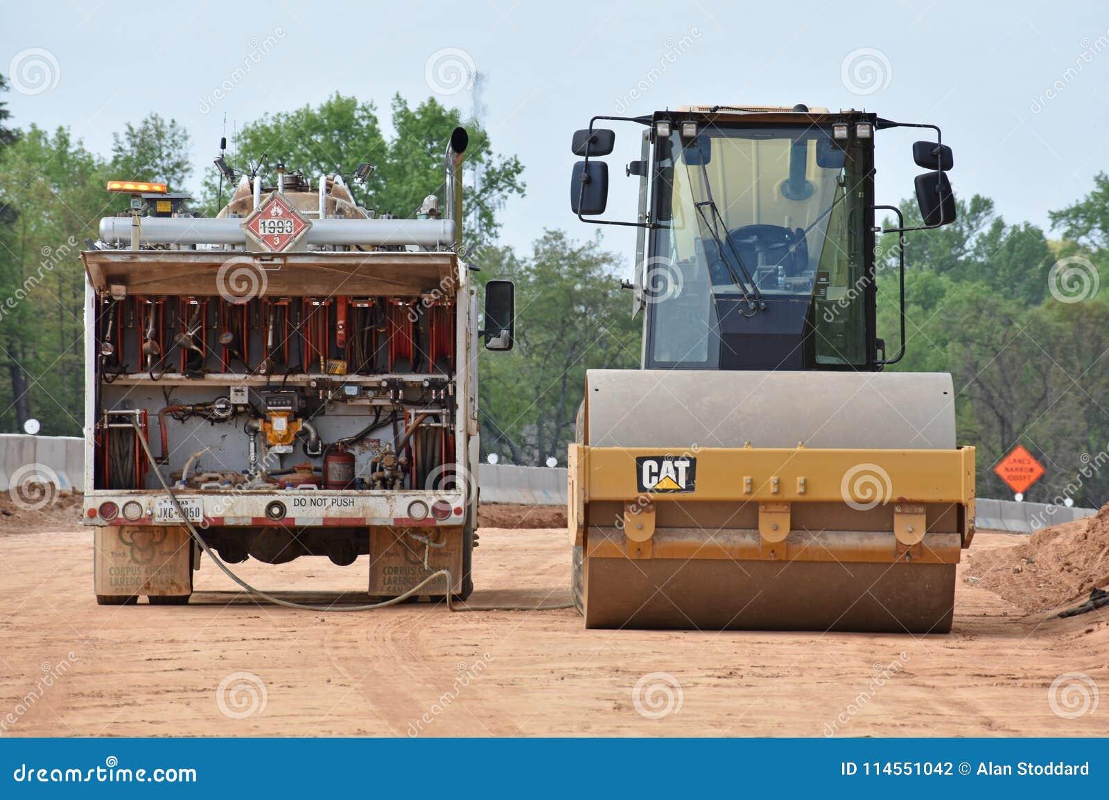Roller machine gets refueled by fluids truck