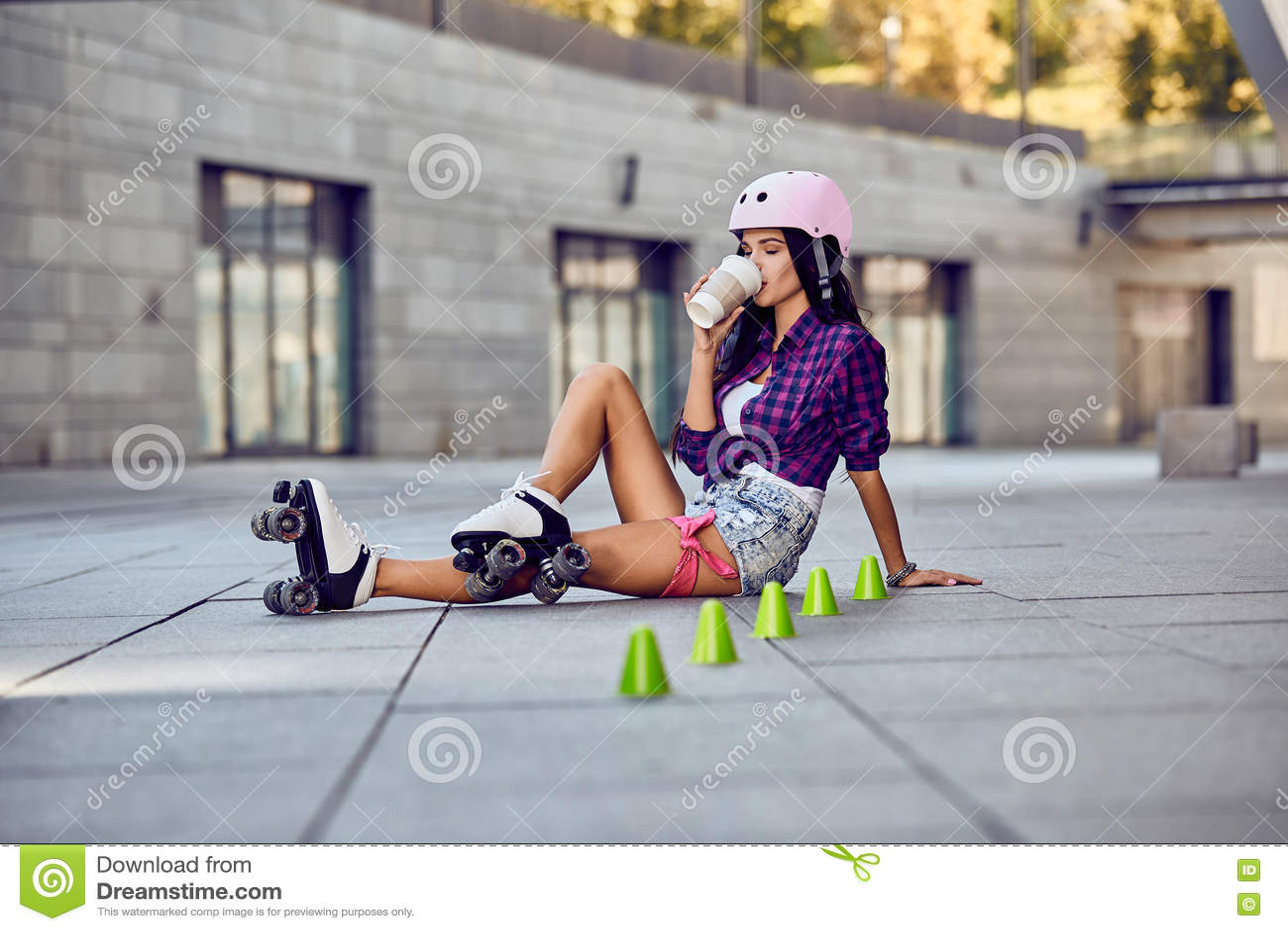 Rollerblading sammanträde för lycklig tonåring på gata- och drinkkaffe