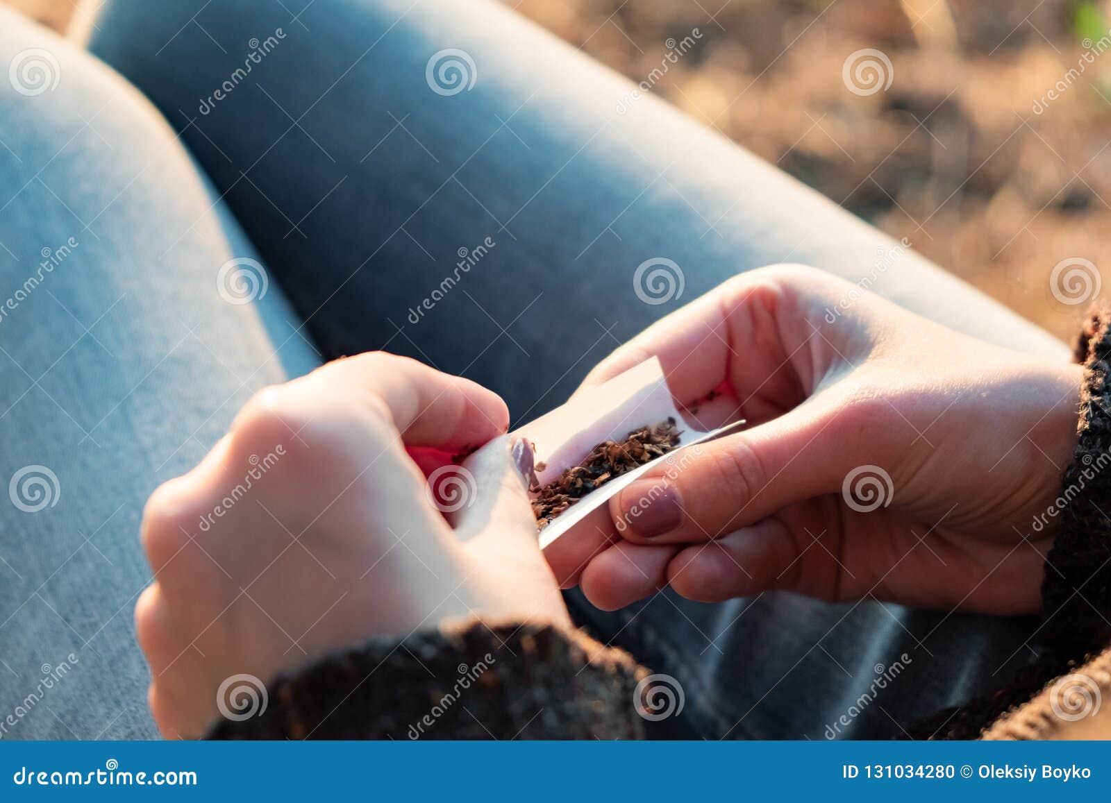 Rolling van een tabakssigaret Sluit omhoog beeld van vrouwelijke handenmaki
