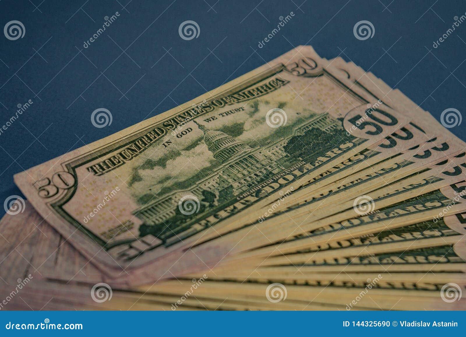 Rollo gordo grande del dinero en un fondo azul
