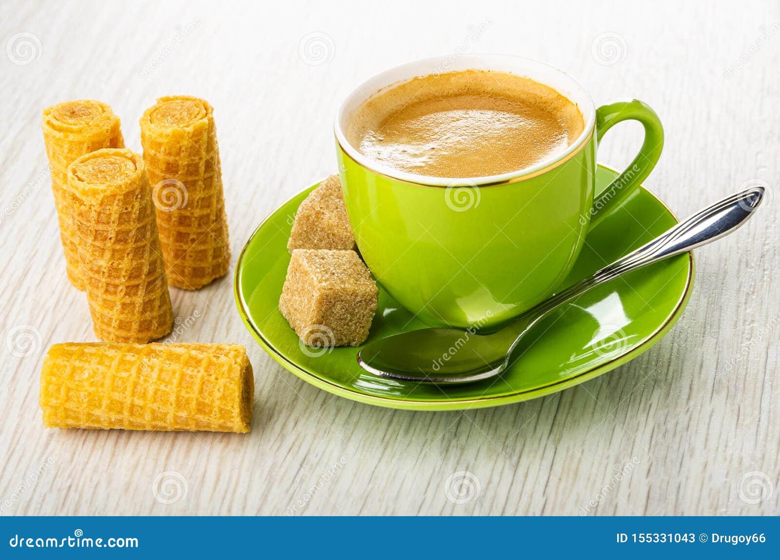Rollos de la oblea, taza verde con el café, cuchara, azúcar en el platillo en la tabla de madera