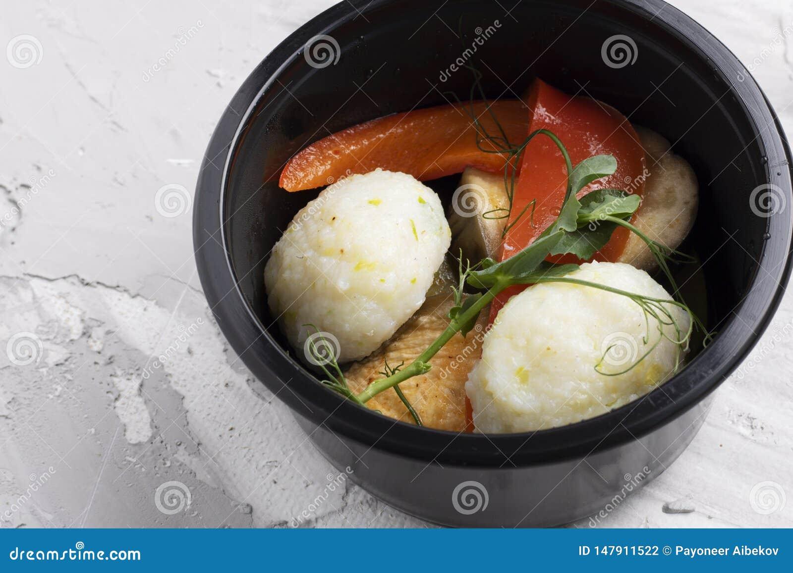 Rollos de las verduras, lentejas y pescados cocidos al vapor con perejil en envase de comida plástico negro