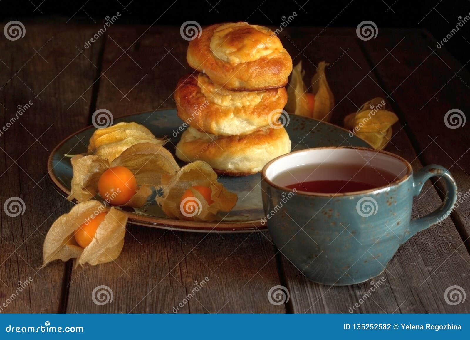 Rollos hechos en casa con requesón y physalis y una taza de té en una tabla de madera