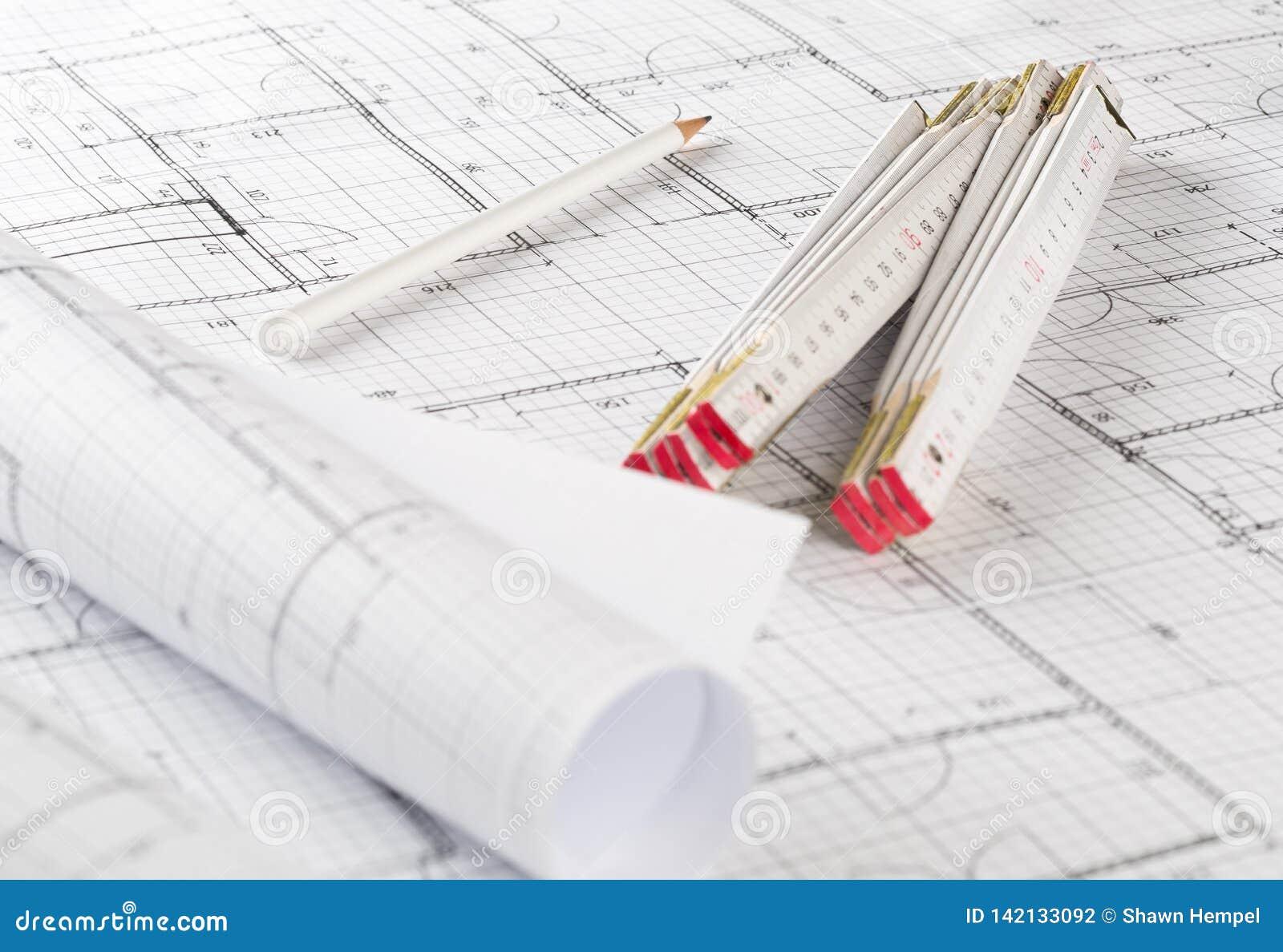 Rolls архитектурноакустических планов жилищного строительства светокопии с правителем карандаша и складчатости на предпосылке све