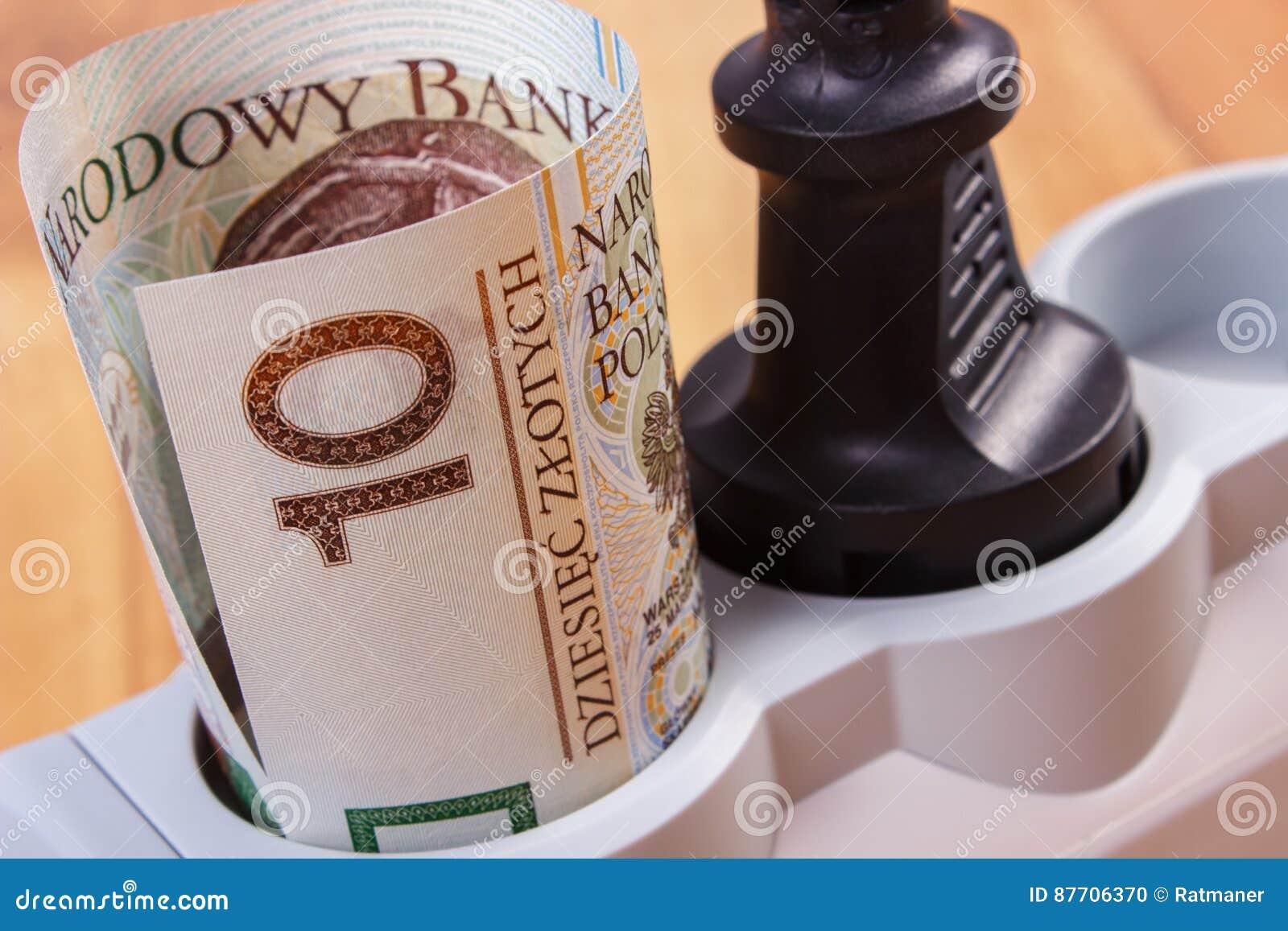 Rolls d argent polonais de devise dans la bande de courant électrique avec la prise reliée, coûts énergetiques