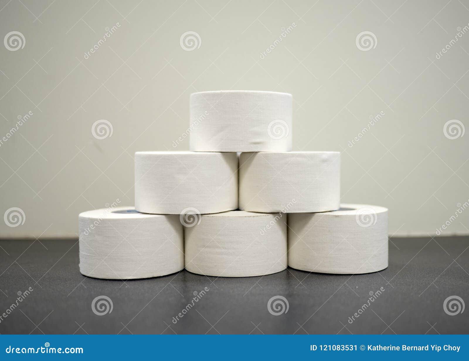 Rolls da fita atlética branca do óxido de zinco em uma pilha