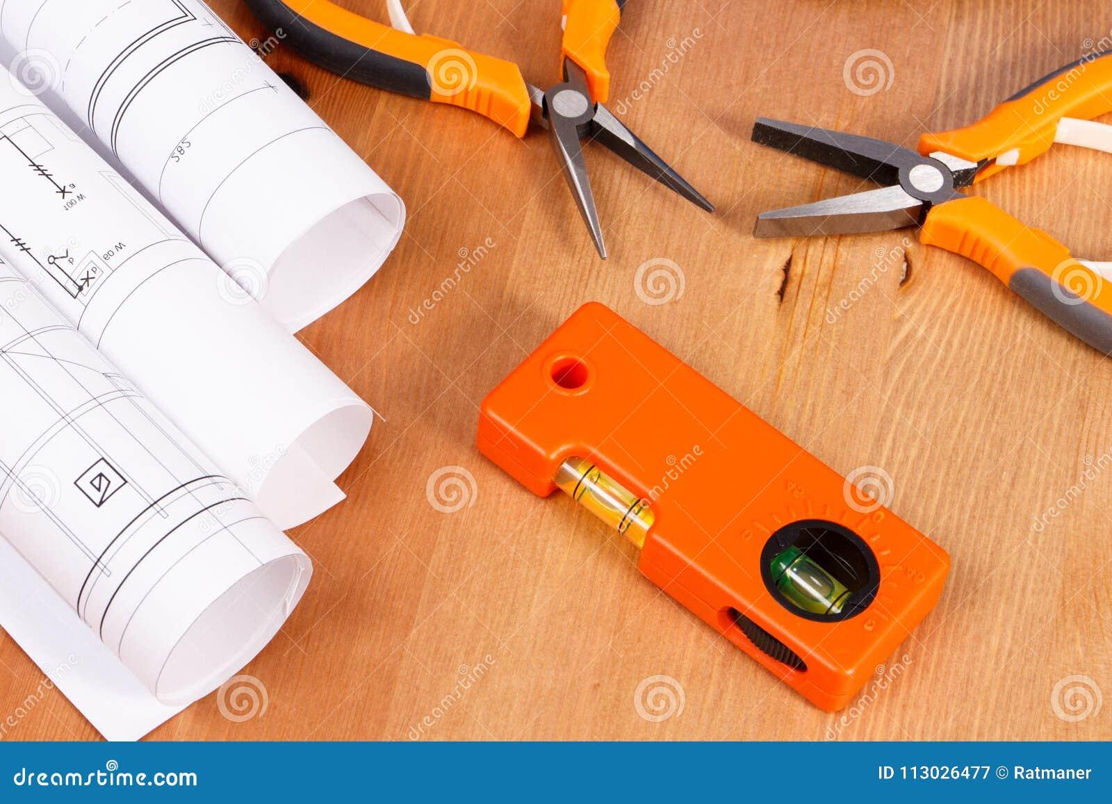 Rolls de dibujos o de modelos eléctricos y herramientas anaranjadas del trabajo para el uso en los trabajos del ingeniero que mie