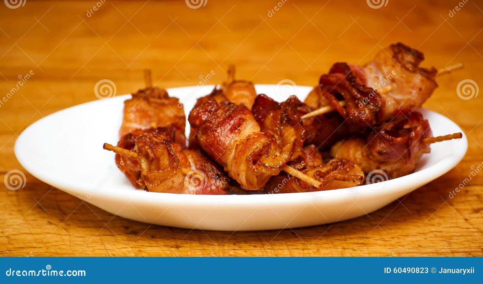Rolls delle fette di oggetto cucinato del bacon con gli stuzzicadenti su un wh