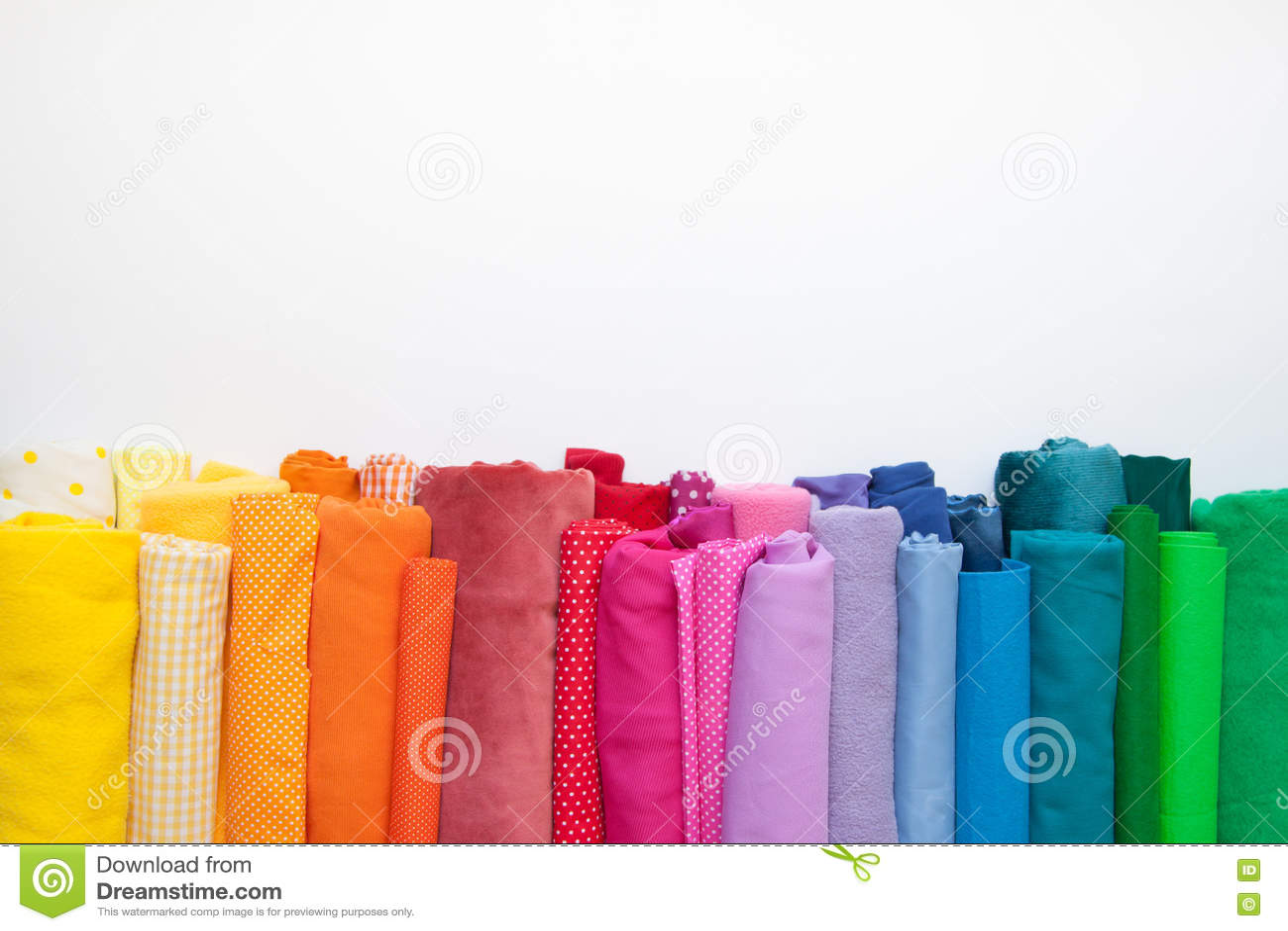 Rolls di tessuto colorato luminoso su un fondo bianco