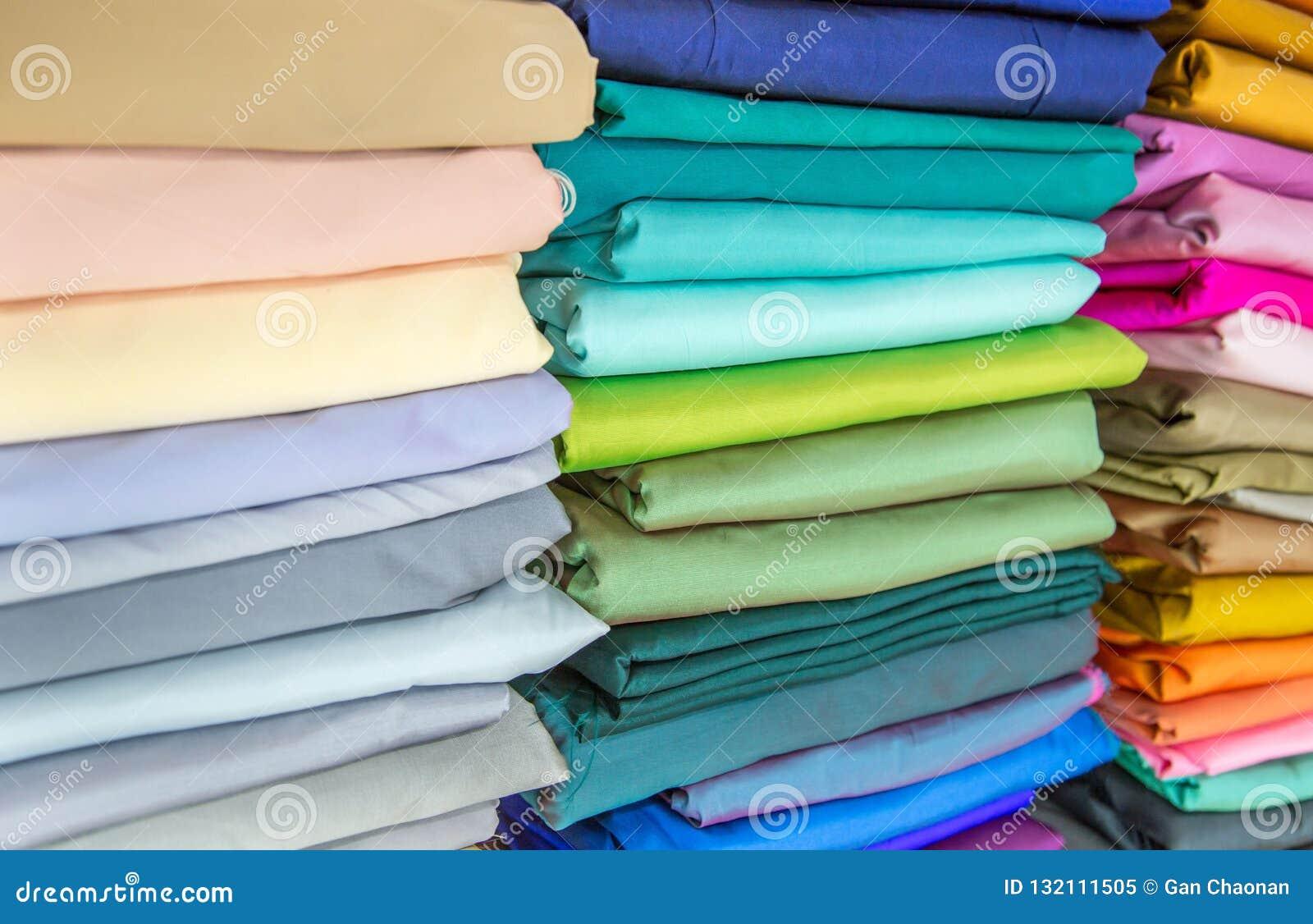 Rolls di tessuto ed i tessuti in una fabbrica comperano o immagazzinano o bazar