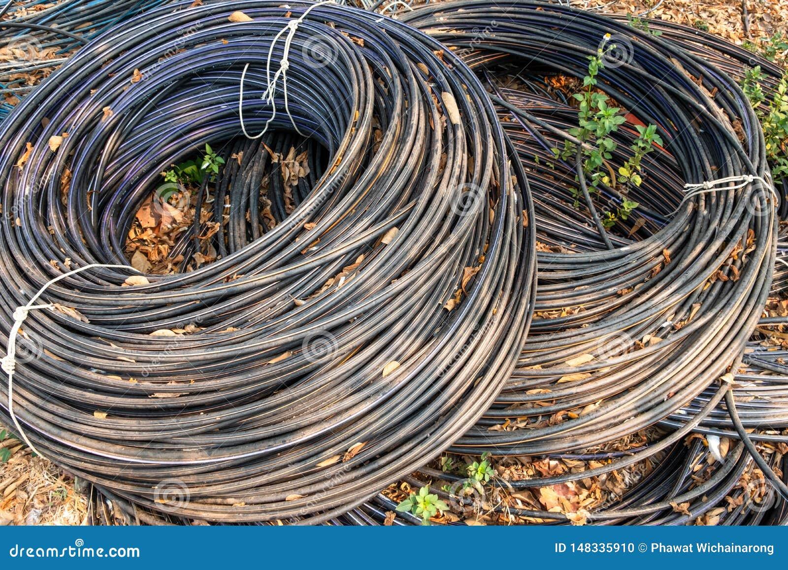 Rolls dos cabos pretos da telecomunicação que encontram-se na terra
