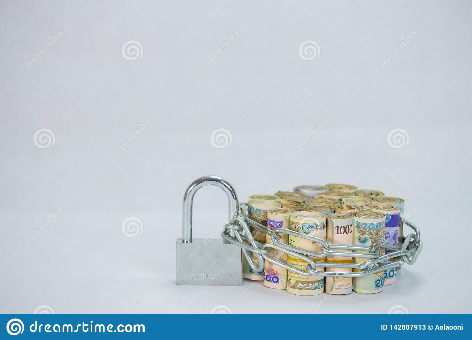 Rolls of Naira Cash local currencies with chain and padlock