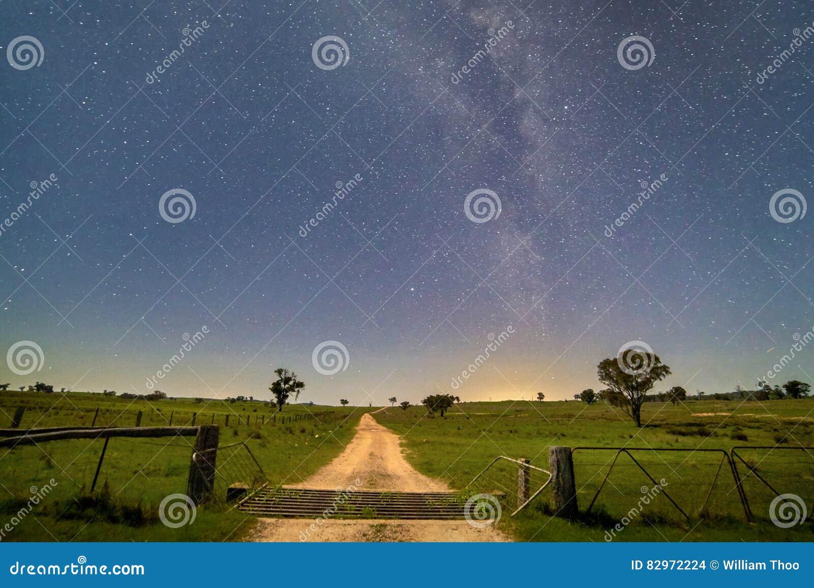 Rolna droga przez bramy i poly przy nocą pod milky sposobem w środkowo-zachodni Nowych południowych waliach, Australia
