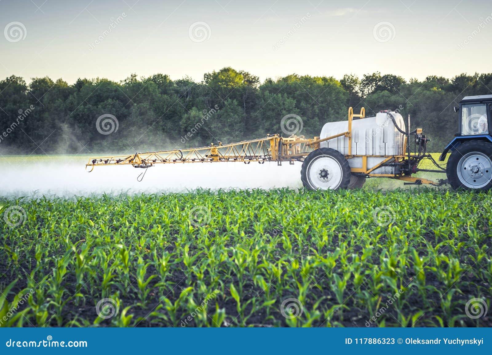 Rolnik na ciągniku z ciągniętą natryskownicą robi użyźniaczowi dla młodej kukurudzy w postaci microdroplets