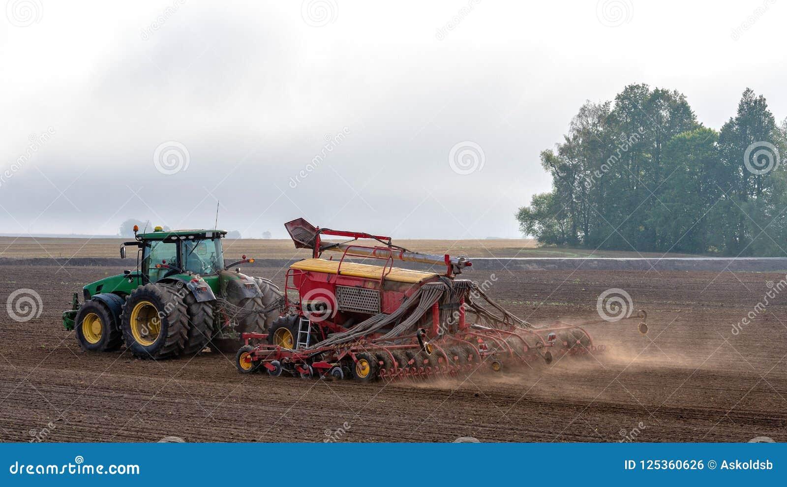 Rolnik w jesieni taktuje pola z ciągnikiem i bogaci one z kopalnymi użyźniaczami