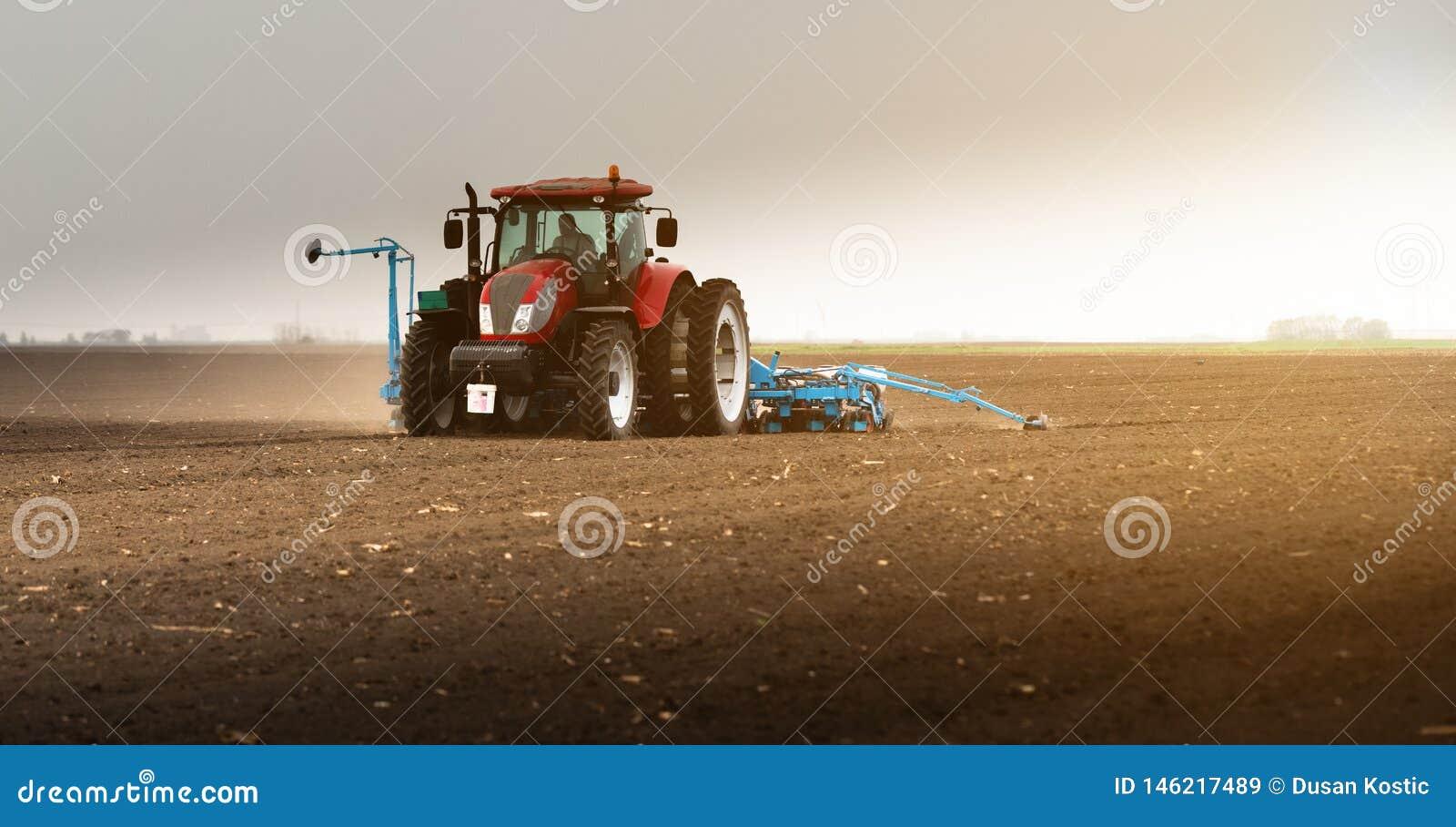 Rolnik z ci?gnikowymi obsiewanie soj uprawami przy rolniczym polem
