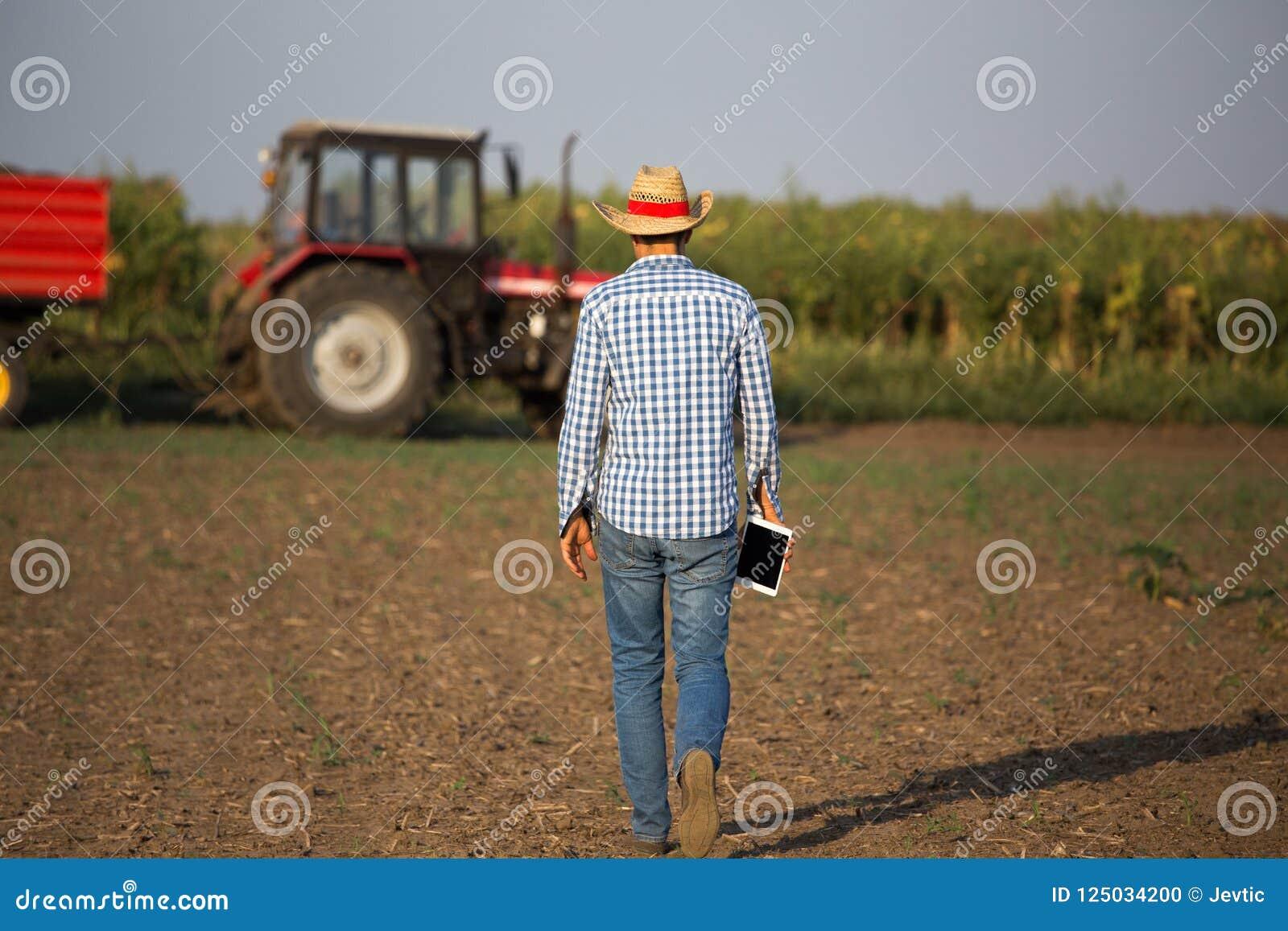 Rolnik z pastylką przed ciągnikiem