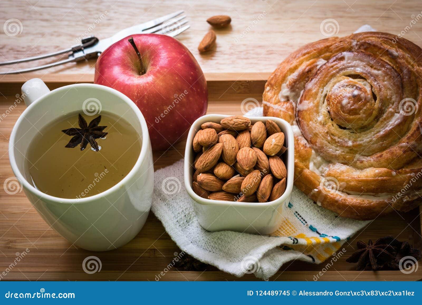 Rolo do café da manhã, chá, maçã, almods com backgroud de madeira
