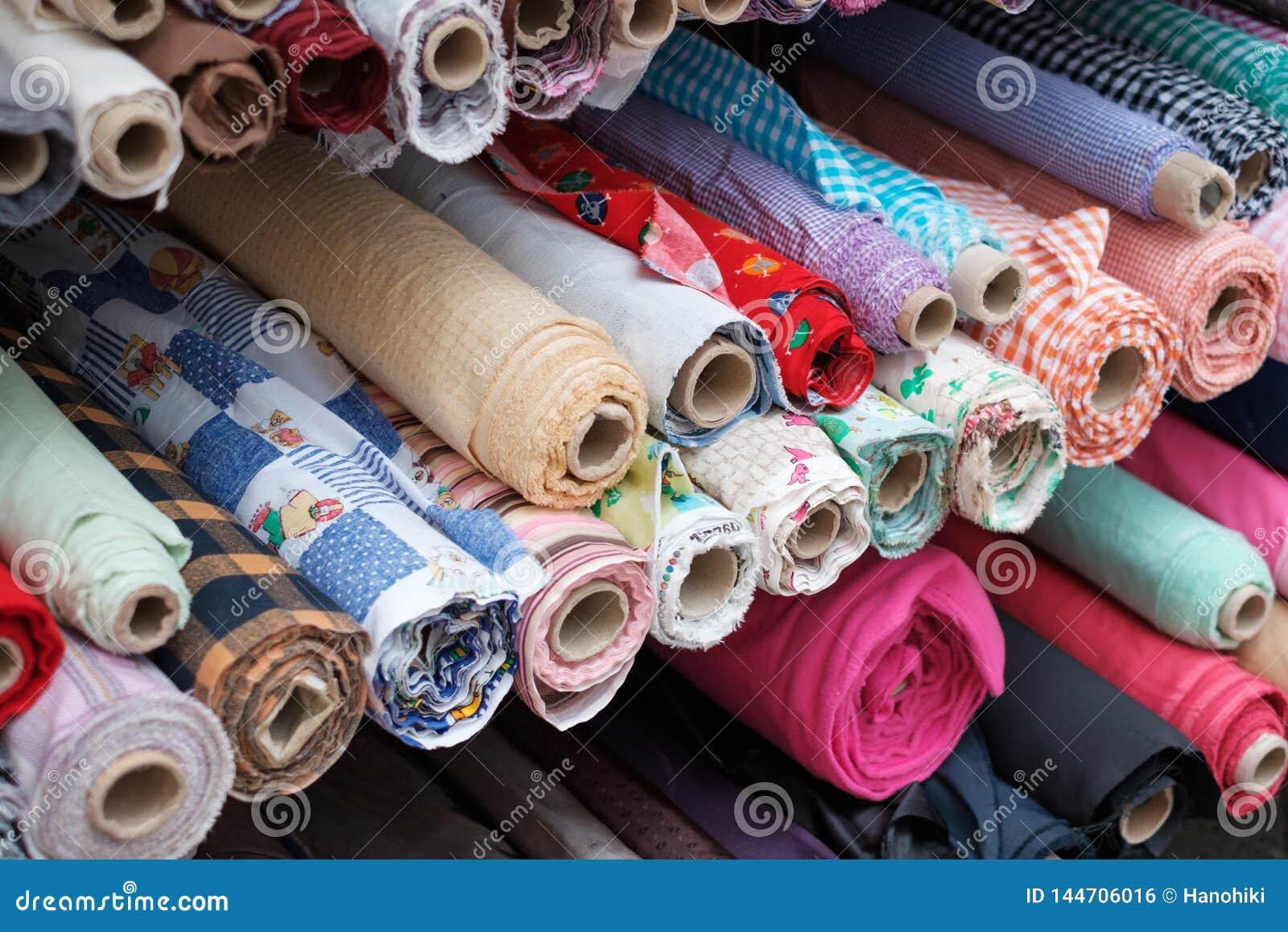 Rolos da tela e matérias têxteis coloridas no suporte do mercado