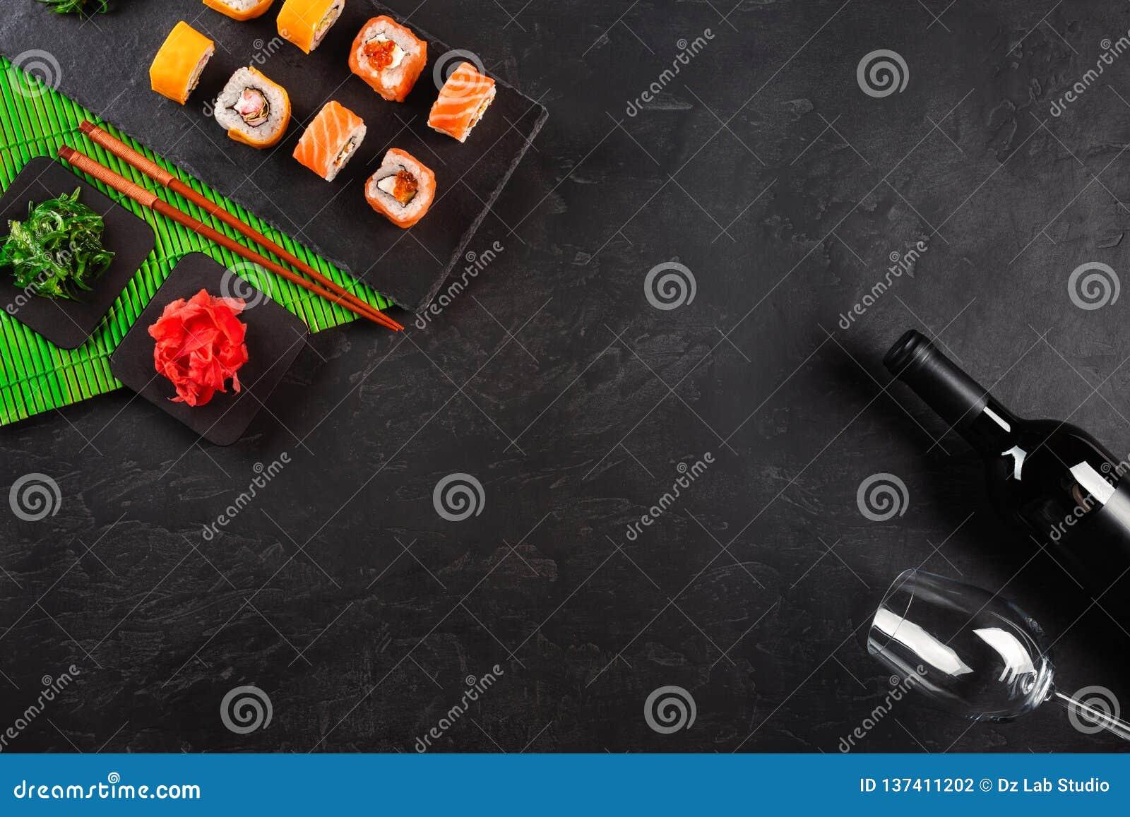 Rolos do sashimi e de sushi do grupo do sushi, garrafa do vinho e um vidro servido na ardósia de pedra