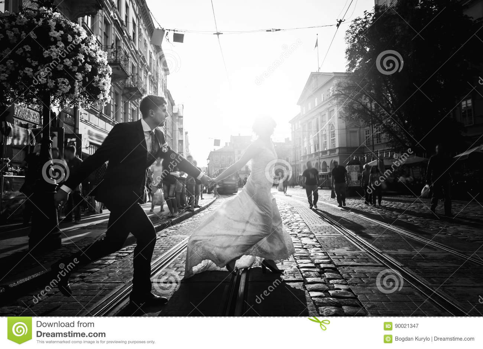 Romântico, pares do recém-casado do divertimento que correm através de pavimentar a estrada na cidade