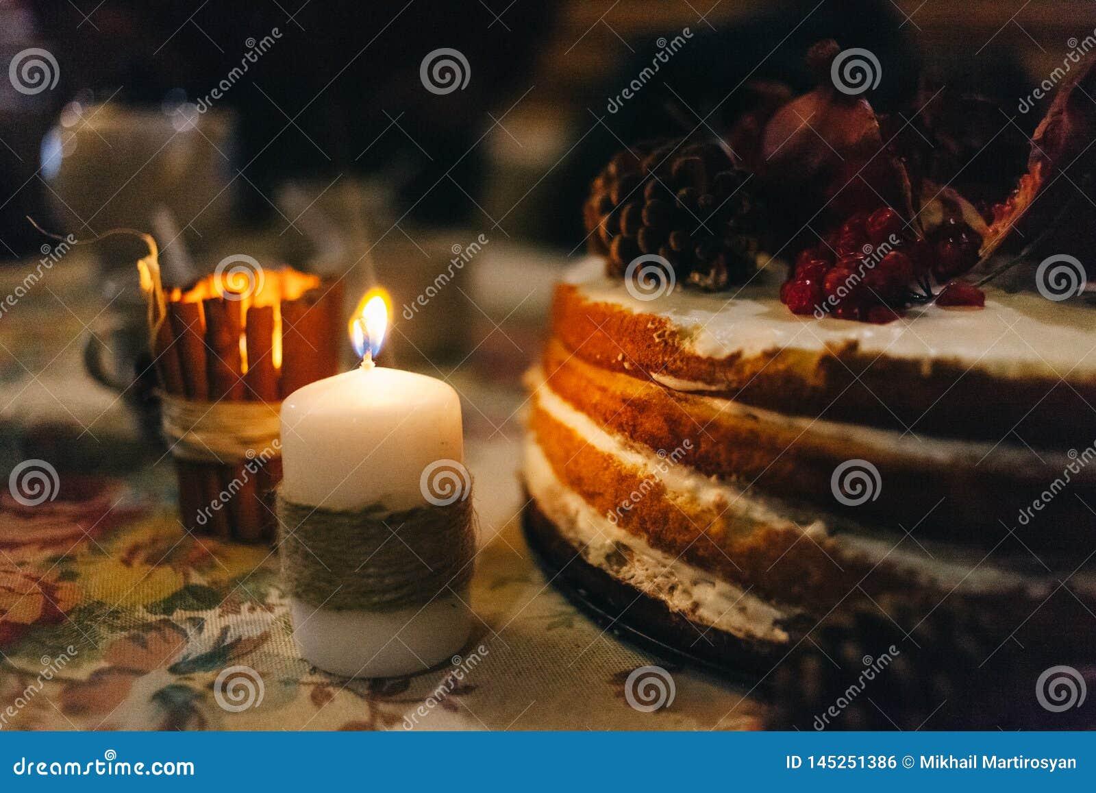 A romã mergulhou o bolo à vista de uma vela grossa da cera envolvida em um cabo do cânhamo